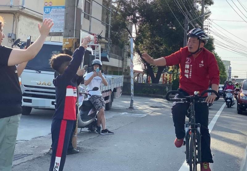 台灣基進陳柏惟昨天打敗顏寬恒寫下驚奇,今天騎單車進行謝票,沿途許多民眾跟他打招呼、擊掌。(記者陳建志翻攝)