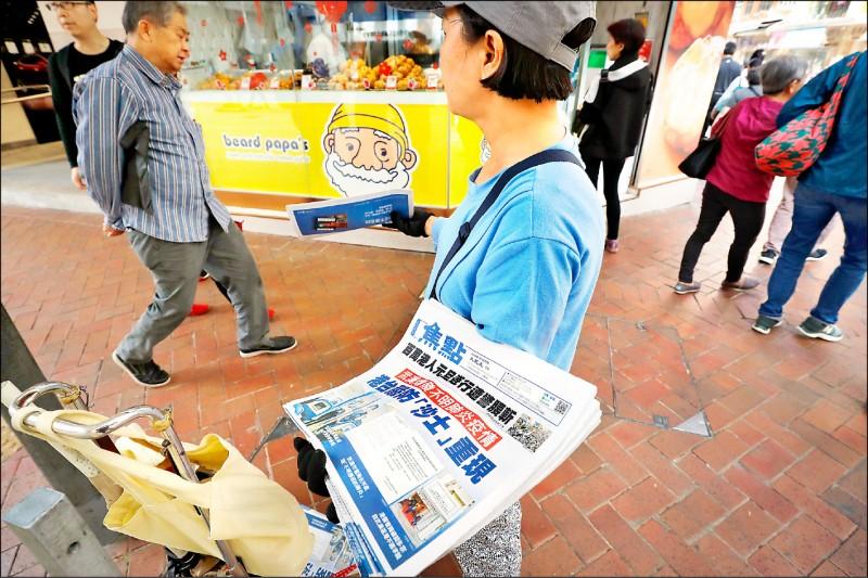 香港小販兜售的報紙,頭版寫著「武漢爆發不明肺炎疫情」。(美聯社)