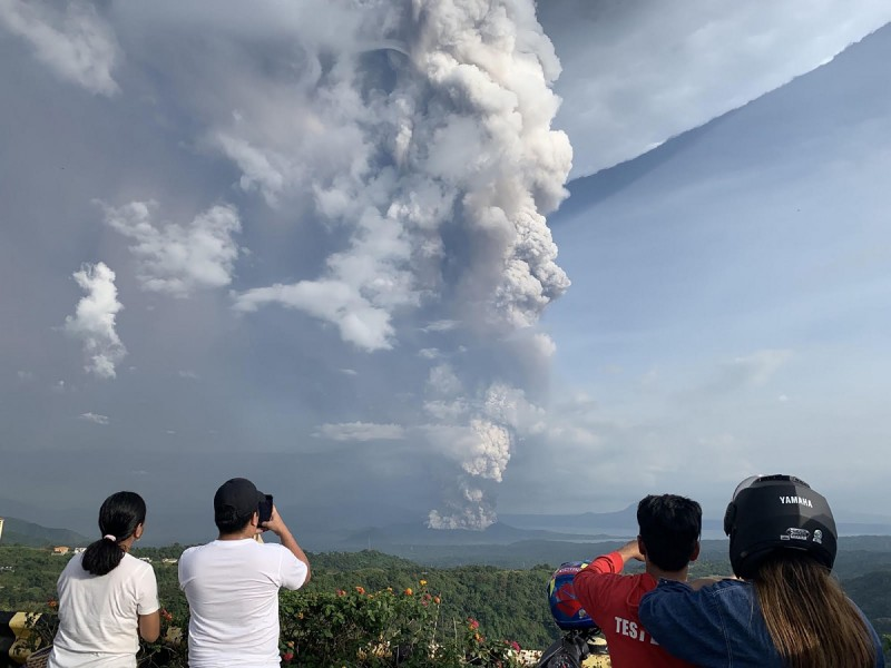 菲律賓的塔爾火山在今日下午噴發,附近島嶼的民眾拍照。(法新社)