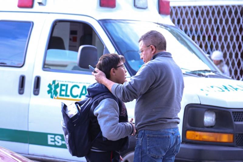 墨西哥小學發生槍擊案,1名11歲男童持槍進入校園後射殺1名女教師並自戕,現場另有6人受傷。圖為槍擊案發生後,家長在校園外接回小孩。(法新社)