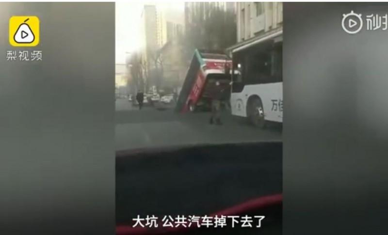 中國青海西寧市大街上道路塌陷,出現大坑洞,整部公車摔進去。(圖擷取自網路影片畫面)