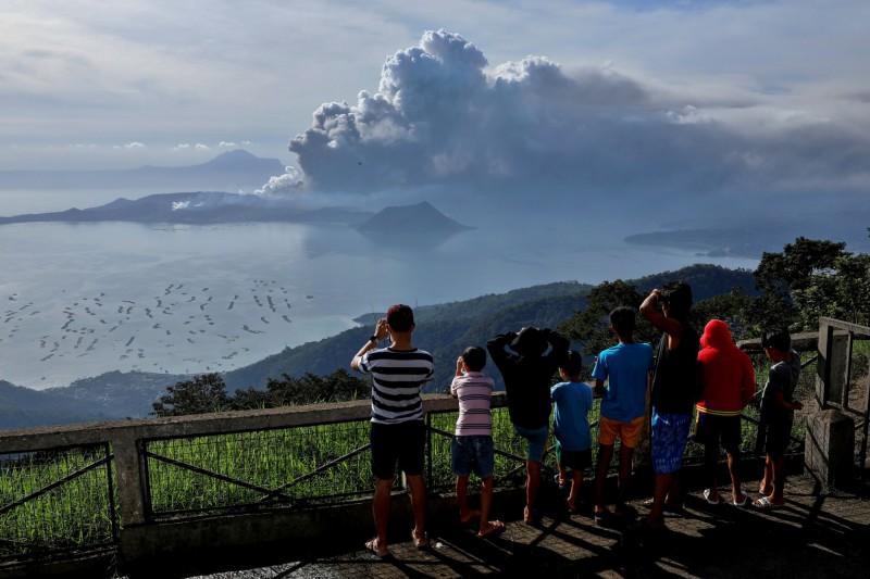 塔爾火山噴發讓當地居民十分緊張,但也有部分觀光客反其道而行,前往靠近火山的城鎮,只為了找到更進更好的角度觀賞這番「奇景」。(路透)