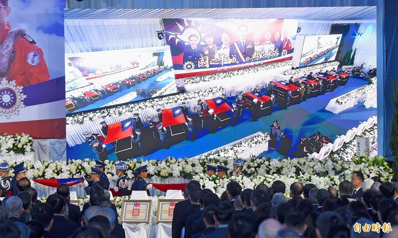 Military personnel yesterday place Republic of China flags on the coffins of late chief of the general staff general Shen Yi-ming and seven other officers during a memorial service at Songshan Air Force Base in Taipei.   Photo: Liao Chen-huei, Taipei Times
