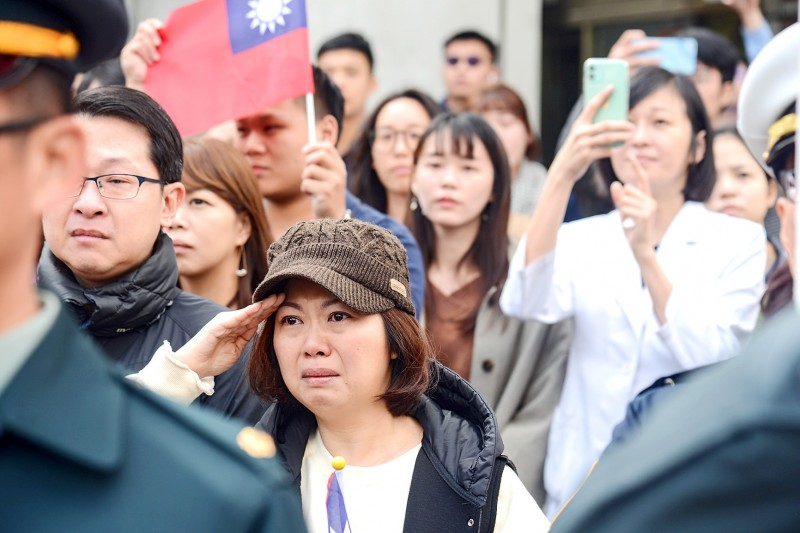 People in the street yesterday pay respects to late chief of the general staff general Shen Yi-ming and seven other officers as hearses carrying their remains move through downtown Taipei after a memorial service at Songshan Air Force Base.  Photo: CNA