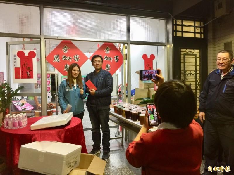 台北市議員(左)陳怡君今晚幫網路紅人「小商人」發雞排,吸引數以百計的民眾排隊。後方貼著是「小商人」新印製的「拿麼厲害」春聯。(記者陳璟民攝)