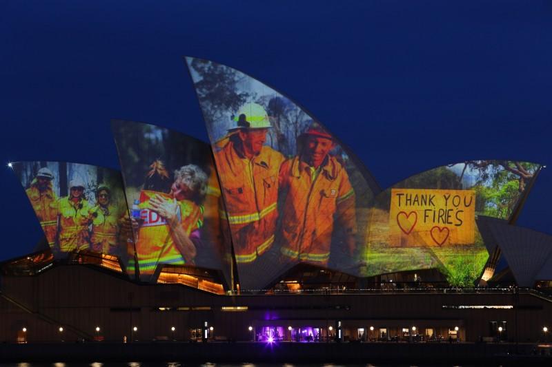 澳洲當地時間11日晚上8點半,雪梨歌劇院點亮外觀,投影在野火季中辛勤救火的消防員照片,以表達敬意。(路透)