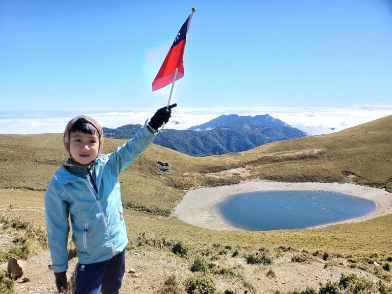 7歲阿興(見圖)與5歲阿賢兄弟本月初與父母登上海拔3000多公尺的三叉山和嘉明湖,在湖畔揮舞國旗,讓網友直呼萌翻了。(邱德鑫提供,中央社)