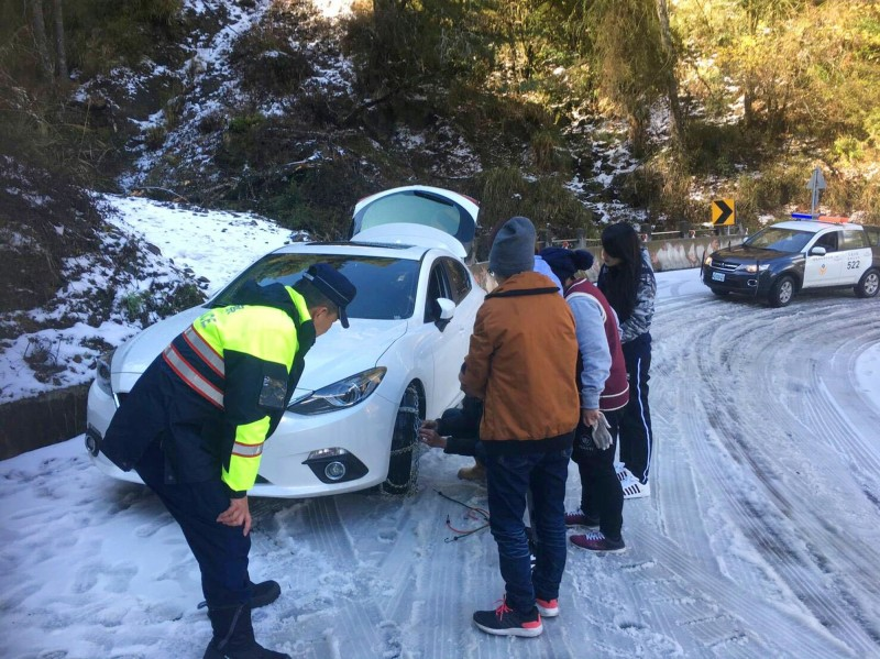 仁愛警方協助上合歡山的車輛加掛雪鏈。(仁愛警方提供)