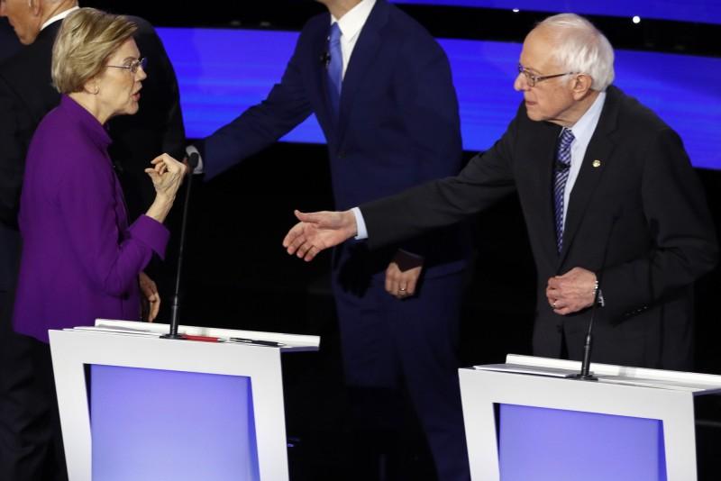 美國民主黨今日進行初選辯論會,參選人華倫(左)被捕捉到拒絕與桑德斯(右)握手。(美聯社)