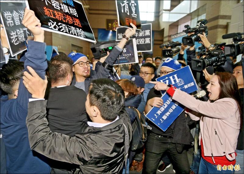 國民黨青年軍高舉「清黨」、「老賊下台」標語表達立場,並與中常委林杏兒(右,粉紅衣)爆發口角,和黨部人員爆發推擠肢體衝突,場面混亂。(記者張嘉明攝)