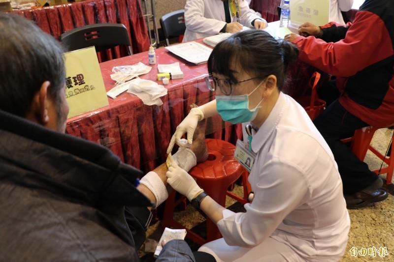 台北醫院醫療團隊為街友看病換藥。(記者周湘芸攝)