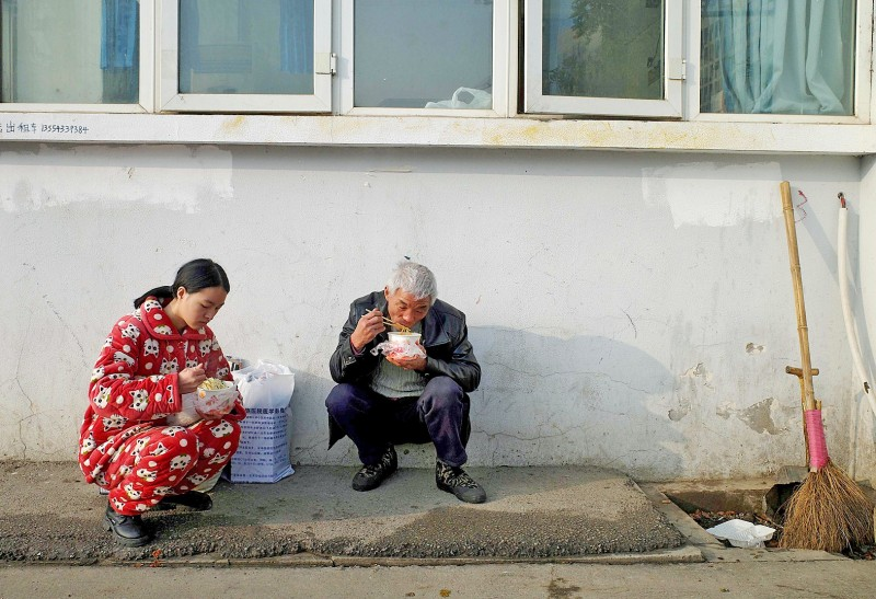 People eat noodles outside the Wuhan Medical Treatment Center, where a man who died from viral pneumonia was confined, in Wuhan, China, on Sunday. Photo: AFP