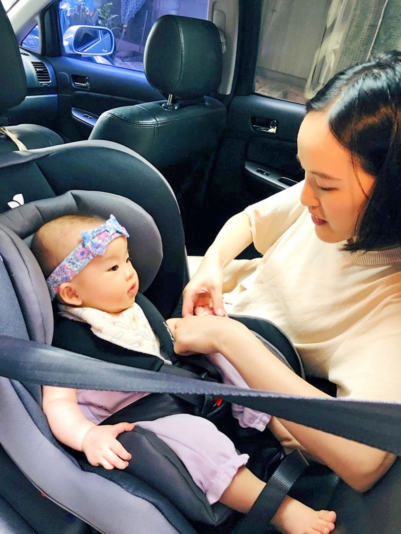 A woman fastens her child in a rear-facing safety travel seat in an undated photograph. Photo provided by a reader