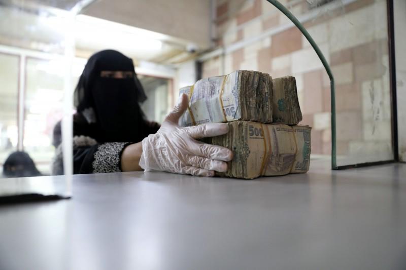 位於沙那的葉門中央銀行,一名職員拿著好幾捆的葉門里亞爾鈔票。(路透)