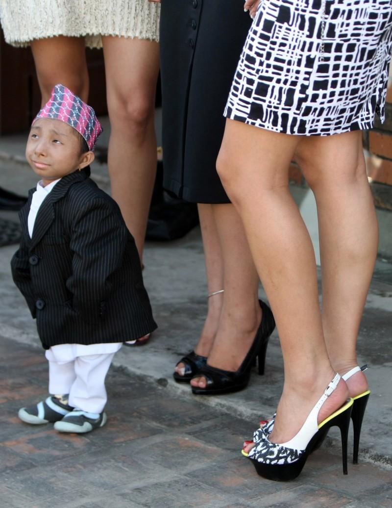 馬加爾身高只到長腿美女的膝蓋。(法新社)