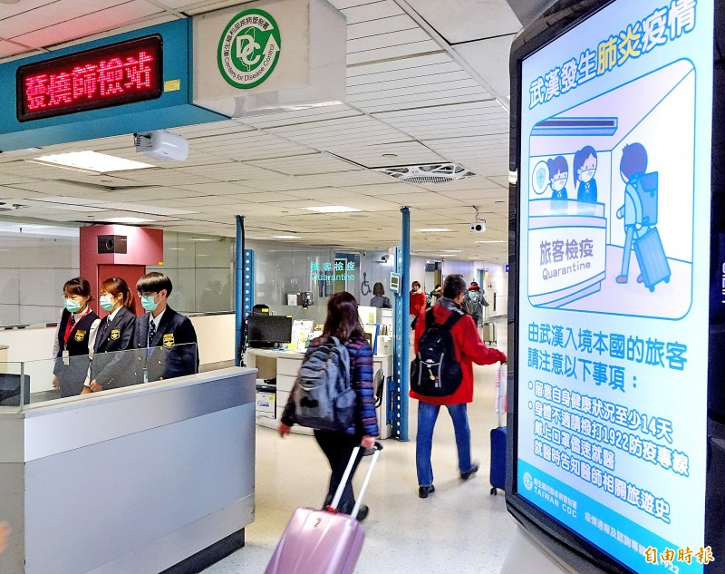 Travelers entering Taiwan pass a poster warning about the virus outbreak in Wuhan on their way through a screening station at Taiwan Taoyuan International Airport yesterday. Photo: Chu Pei-hsiung, Taipei Times