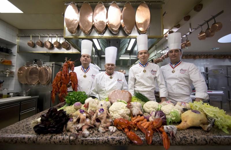 法國已故料理「教皇」博古斯(Paul Bocuse,左二)的餐廳L'Auberge du Pont de Collonges,從1955年以來就一直保持著米其林3星,但在今年被降為2星,結束55年的3星榮耀。圖為博古斯2016年在L'Auberge du Pont de Collonges廚房與大廚們合照。(歐新社)