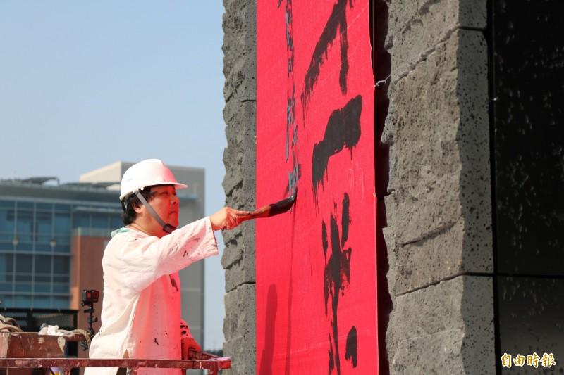 書法家陳世憲站上升降車凌空揮毫,為南科考古館題詞寫春聯。(記者萬于甄攝)