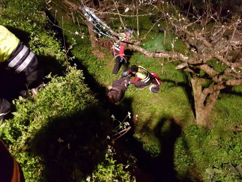 傷者墜落路旁果園,消防人員急救援。(圖:苗栗消防局提供)
