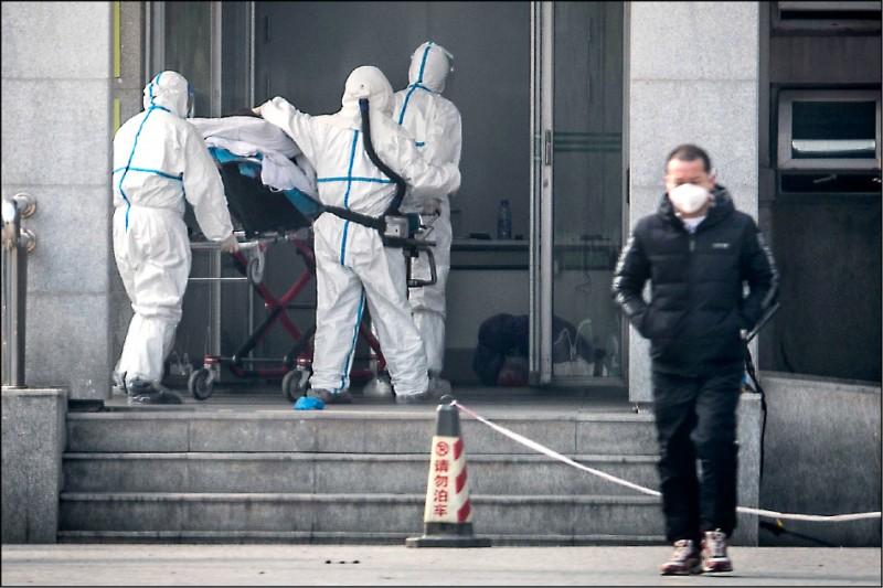 武漢市醫護人員昨日把感染新型冠狀病毒的病患送到金銀潭醫院治療。(法新社)