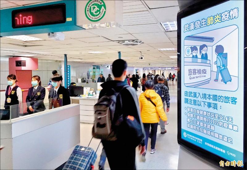 中國武漢爆發不明肺炎疫情,疾管署在桃園機場入境旅客發燒篩檢站旁設置電子看板,提醒自武漢入境民眾多加注意。(記者朱沛雄攝)