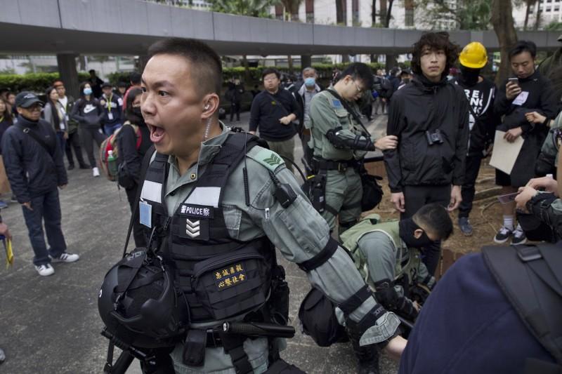 大批防暴警察在集會現場攔查市民及記者,更將記者的身分證拿到鏡頭前直播。(美聯社)
