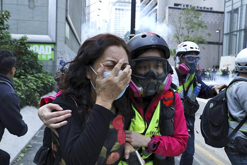 A woman cries yesterday as she pleads with Hong Kong police not to beat a man as police detain protesters calling for electoral reforms and a boycott of the Chinese Communist Party. Photo: AP