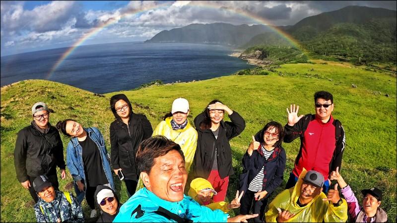 彩虹通常高掛天邊、遙不可及,蘭嶼椰油國小教師群前天在島上的青青草原研習,驚見完整的彩虹近在眼前,落地掛在崖邊,就像彩虹橋,像是可以觸摸、跨越似的。(圖:記者黃明堂翻攝)
