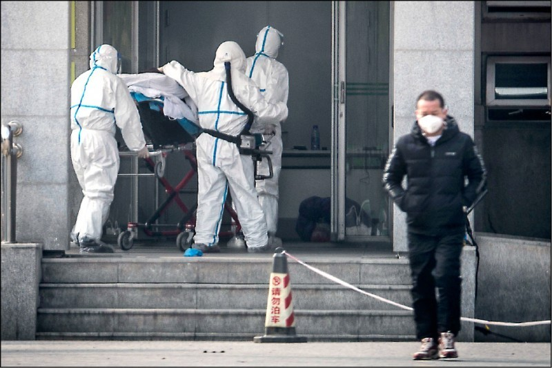 武漢市醫護人員19日把感染新型冠狀病毒引起肺炎的病患送到金銀潭醫院治療。(法新社)