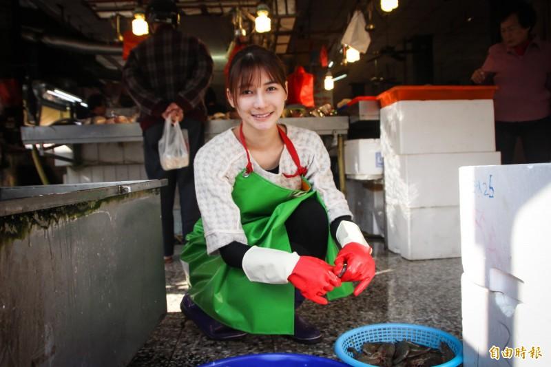 「最美魚販」劉芃芃(阿澎),返鄉幫忙賣魚、剝蝦。(記者陳冠備攝)
