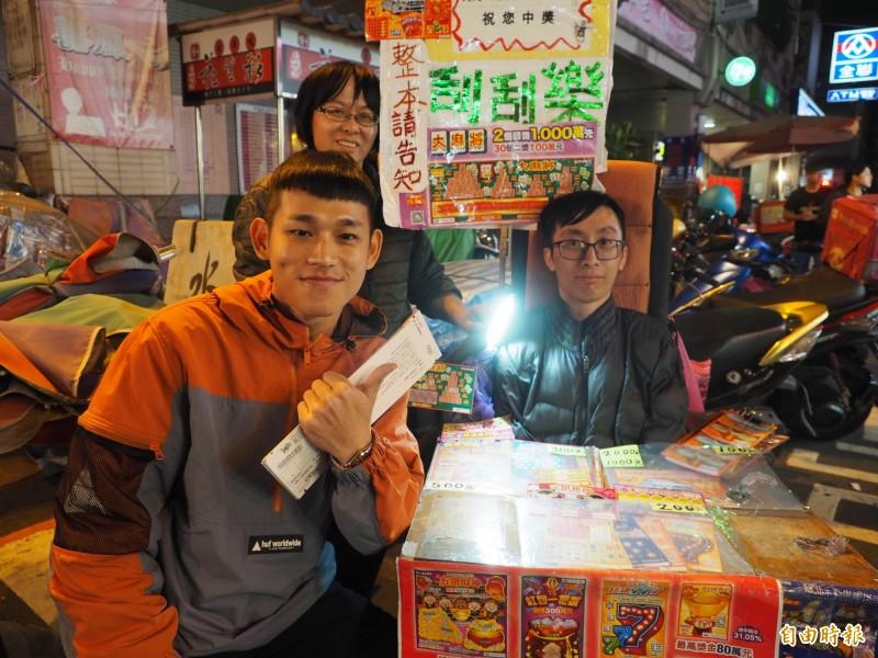 「草屯囝仔」的阿倉自己買,也幫老闆「玖壹壹」買彩券,開心地跟蔡承恩和蔡媽媽合照,並答應過兩天會再送他們的簽名海報過來。(記者陳鳳麗攝)