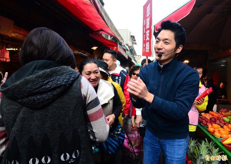 國民黨立委蔣萬安到長春市場謝票,蔣萬安(中)一一跟民眾和攤商握手鞠躬致意。(記者王藝菘攝)