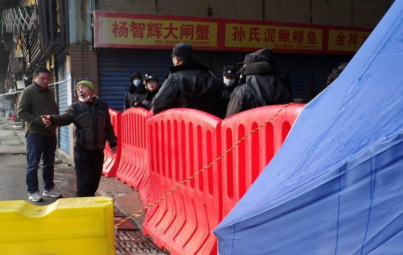 武漢肺炎最初傳出疫情的華南市場周圍居民、店主普遍未戴口罩。(法新社資料照)