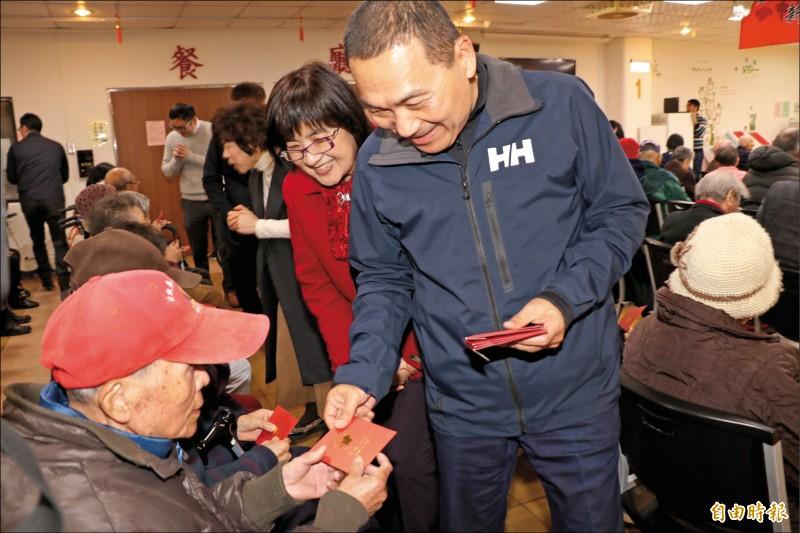 新北市長侯友宜(右)昨日下午到汐止區翠柏新村老人安養中心發放小福袋。(記者俞肇福攝)