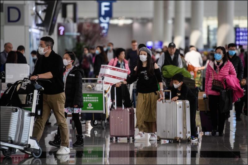 中國武漢新型冠狀病毒肺炎疫情迅速在國際擴散,繼日韓、台灣及泰國出現確診病例後,美國、香港、澳門二十二日均出現首例確診。圖為香港國際機場不少旅客已戴上口罩。(法新社)