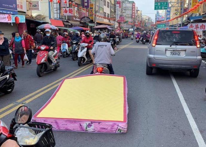 有網友捕捉到一幕驚人畫面,一名女騎士竟然將床墊直接綁在機車後頭,用拖行方式運送,讓不少網友相當驚訝。(圖擷自爆廢公社公開版)