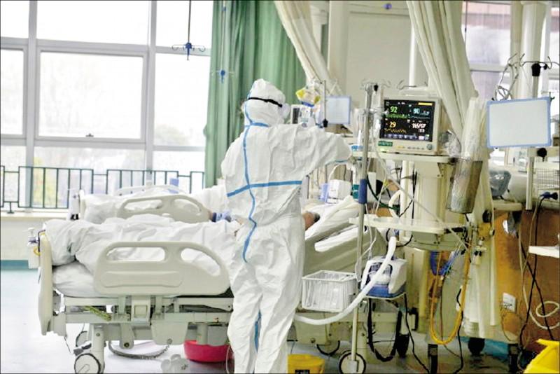 中國湖北省武漢市「中心醫院」公布的照片顯示,該院一名醫護人員穿戴防護裝備,正在查看一名疑似新型冠狀病毒肺炎患者的病情。(路透)