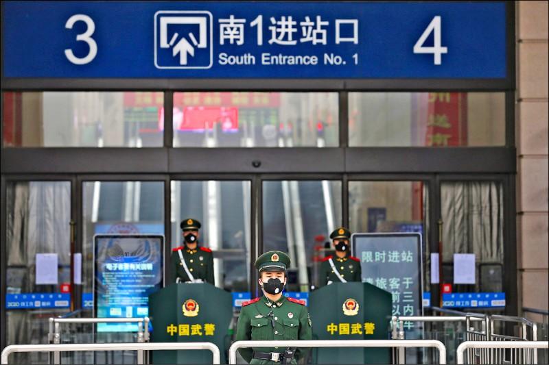 3名中國武警昨日守在武漢市漢口火車站外,執行當局下達的封城令。(美聯社)