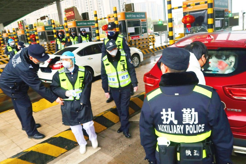 Police officers wearing masks yesterday check the trunk of a car for smuggled wild animals at an expressway toll station in Xianning, a city to the north of Wuhan, China. Photo: Reuters