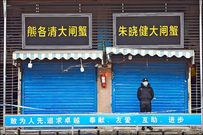 一名戴著口罩的警衛廿四日留守於武漢肺炎病毒源頭、湖北武漢的華南海鮮批發市場。(法新社)