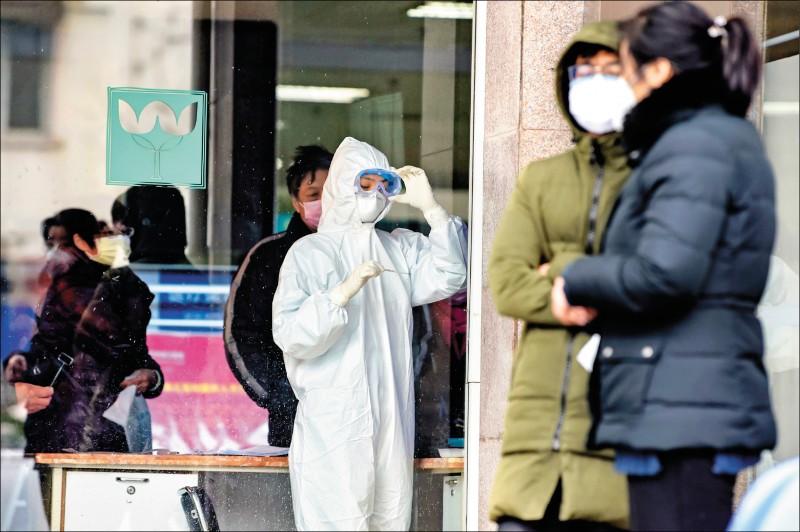 武漢肺炎升溫,一名身著防護裝的護士,昨日在中國湖北省武漢市第五醫院檢查溫度計。(法新社)