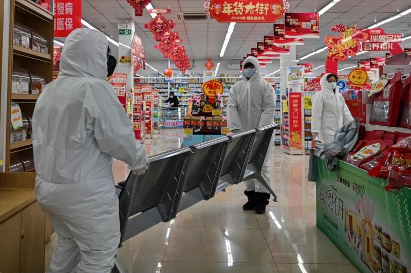 圖為武漢一間超市身著防護衣的工作人員。(法新社)