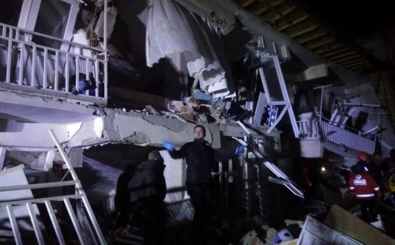 救援人員站在倒塌的建築物外。(路透)