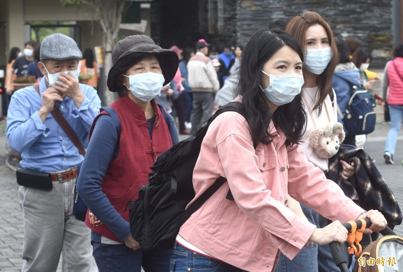 中國武漢肺炎疫情蔓延,不過大年初一天氣尚可,許多民眾戴著口罩出遊(見圖),但大年初二回娘家,全台都有可能下雨,出門記得帶雨具。(記者簡榮豐攝)