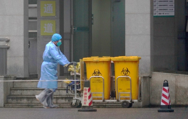 中國湖北省衛生當局今天通報,感染「2019新型冠狀病毒」新增15個死亡病例,目前累積至39人。圖為一名工作人員推動生物廢棄物容器通過武漢醫療中心的入口。(美聯社)
