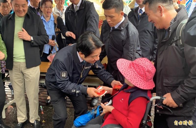 賴清德彎下身拿福袋給坐輪椅的阿嬤並向她賀年。(記者陳鳳麗攝)