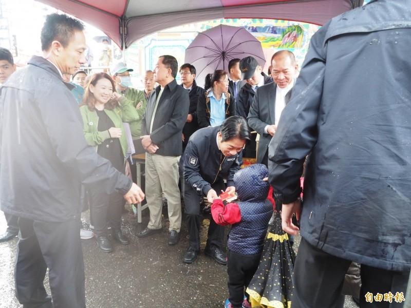 小小孩冒雨領福袋,賴情德彎下身來拿給他。(記者陳鳳麗攝)