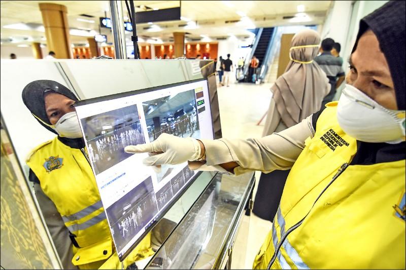 為防堵武漢肺炎,印尼龍目島國際機場的衛生 官員正在檢查入境旅客的體溫。 (法新社)