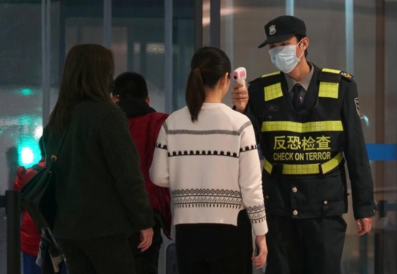 武漢天河國際機場保安人員本月21日為出境旅客量體溫。(美聯社)