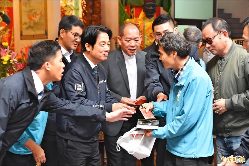 副總統當選人賴清德(左)昨天到雲林虎尾天后宮發送一元福袋。(記者黃淑莉攝)